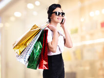 Woman with shopping bags talking on the mobile. Stock Photography