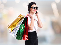 Woman with shopping bags talking on the mobile. Stock Images