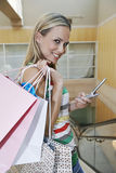 Woman With Shopping Bags Text Messaging Stock Photo