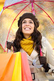 Woman with shopping bags and umbrella in autumn season Royalty Free Stock Images