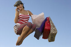 Woman With Shopping Bags Using Cell Phone In Midair Royalty Free Stock Image
