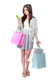 Woman with shopping bags while using mobile phone Royalty Free Stock Photos