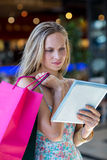 Woman with shopping bags using tablet computer Royalty Free Stock Photography