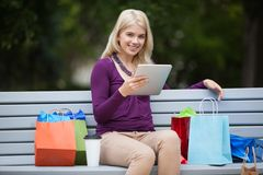 Woman With Shopping Bags Using Tablet PC Outdoors Stock Photos
