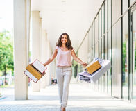 Woman with shopping bags walking on mall alley Royalty Free Stock Photo