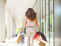 Woman with shopping bags walking on mall alley Stock Photography