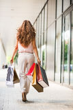 Woman with shopping bags walking on mall alley Stock Photos