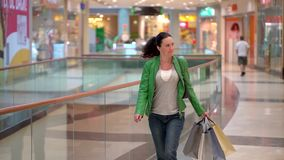 Woman with shopping bags walking in mall. Concept: fashion, sale, shopping, happiness. Woman with shopping bags walking in mall. Concept: fashion, sale stock footage