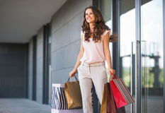 Woman with shopping bags walking out from shop Royalty Free Stock Image