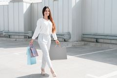 Woman is walking on road near parking after shopping in mall. stock photos
