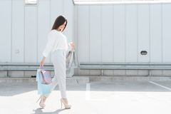 Woman is walking on road near parking after shopping in mall. royalty free stock photography