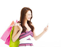 Woman with shopping bags and watching smart phone. Asian woman with shopping bags and watching smart phone Royalty Free Stock Images