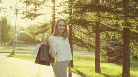 Woman with shopping bags. Young woman with shopping bags smiling and looking at camera in the park stock video footage