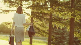 Woman with shopping bags. Young woman with shopping bags walking away looking back in sunshine rays stock footage