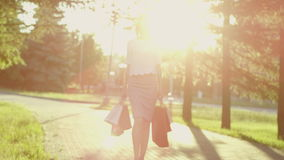 Woman with shopping bags. Young woman with shopping bags walking in the park in sunshine rays stock video