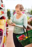 Woman with shopping basket choosing flowerpot Royalty Free Stock Photo
