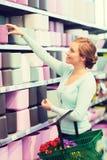 Woman with shopping basket choosing flowerpot Royalty Free Stock Image