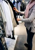 Woman shopping for beautiful modern clothes in casual store Stock Images
