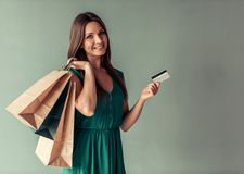 Woman and shopping. Beautiful woman in elegant green dress is holding shopping bags and a credit card, looking at camera and smiling, on gray background Stock Image