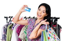 Woman shopping. Beautiful young woman with shopping bags showing credit card or gift card and clothes rack, isolated over white background Royalty Free Stock Photo
