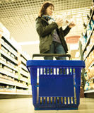 Woman shopping with blue basket at supermarket shop. Retail. Stock Image