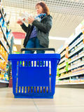 Woman shopping with blue basket at supermarket shop. Retail. Stock Photos