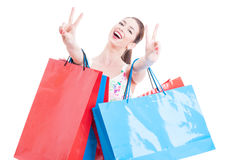 Woman at shopping with bunch of bags showing peace sign Royalty Free Stock Photography