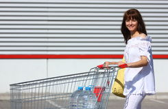 Woman with shopping cart Royalty Free Stock Photography