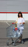 Woman with shopping cart. Woman with a shopping cart carrying two big bottle of water outdoor on a parking Royalty Free Stock Images