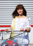 Woman with shopping cart. Smiling woman with a shopping cart carrying two big bottle of water outdoor on a parking close up shot Stock Photo
