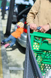 Woman with shopping cart on car parking Royalty Free Stock Photos
