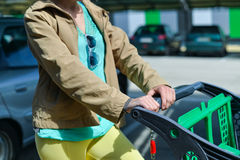Woman with shopping cart on car parking Royalty Free Stock Photo