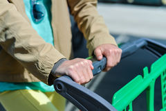 Woman with shopping cart on car parking Stock Photography