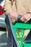 Woman with shopping cart on car parking. Young woman holding shopping push cart closeup picture of hands with car on background Royalty Free Stock Photography