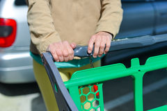 Woman with shopping cart on car parking. Young woman holding shopping push cart closeup picture of hands with car on background Royalty Free Stock Images