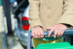 Woman with shopping cart on car parking. Young woman holding shopping push cart closeup picture of hands with car on background Stock Photos