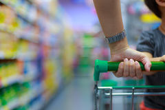 Woman with shopping cart. Closeup of woman with her son sit on hopping cart stock photo