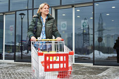 Woman with shopping cart exits the store Royalty Free Stock Image