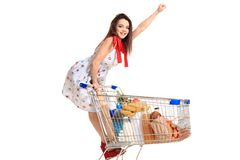 Woman with shopping cart full with products isolated over white background. A young woman rides for fun on an iron shopping basket, raising her hand up like a Royalty Free Stock Photo
