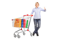 Woman with shopping cart giving thumb up Royalty Free Stock Image