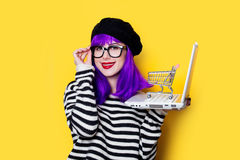Woman with shopping cart and laptop Royalty Free Stock Images