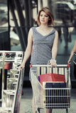 Woman with shopping cart at the mall window Stock Images