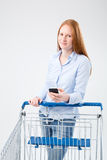 Woman with Shopping Cart and Mobile Phone Stock Images