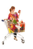 Woman with Shopping cart reading label. Woman with shopping cart full with dairy grocery products reading label  isolated over white background Stock Image