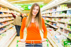 Woman with shopping cart in supermarket Stock Photos