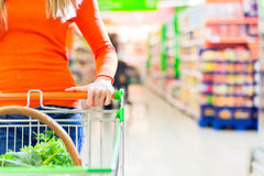 Woman with shopping cart in supermarket royalty free stock photo