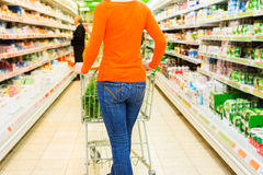 Woman with shopping cart in supermarket Royalty Free Stock Photography
