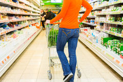 Woman with shopping cart in supermarket Royalty Free Stock Image