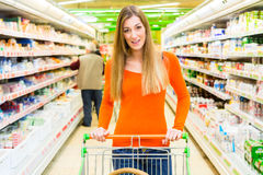 Woman with shopping cart in supermarket Royalty Free Stock Photos