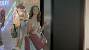 Woman in shopping center with bags. Fashion girl in mall looking on shopwindow background. stock video
